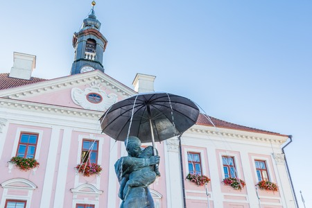 Tartu, Estonia - September 27, 2018: Sculpture of kissing studens under an umbrella in front of the town hall of Tartu in Estonia