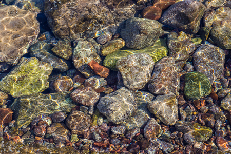 Colorful stones underwater in the sea with reflections of the sun