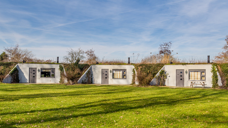 Row of eco lodges build into a Dutch dyke in Gelderland, Netherlands
