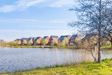Row of modern brick houses along water in a family friendly suburban neighborhood in Veenendaal in the Netherlands. Stockfoto