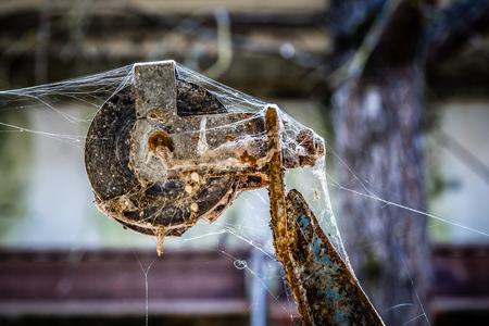 Verrostete Riemenscheibe mit Spinnennetz in einem verlassenen Bauernhof in der Sperrzone von Tschernobyl in Weißrussland, Standard-Bild