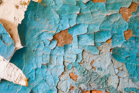 Texture of blue peeling paint on an old wall in an abandoned house