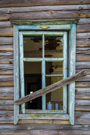 Windows with broken glass of an old abandoned house in Belarus Chernobyl exclusion zone in Belarus