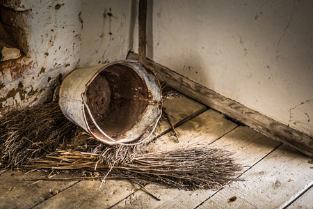 Old rusted bucket and broom in the corner of a abandoned old farm in Belarus, Chernobyl exclusion zone Stockfoto