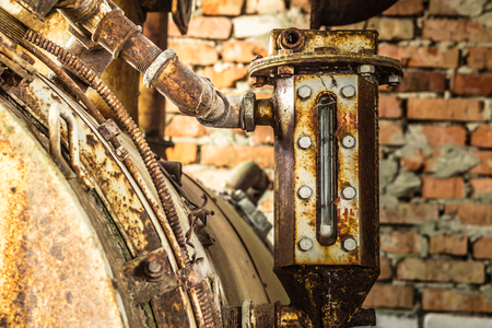 Rusted liquid meter of an ancient machine in a abandoned factory Stockfoto