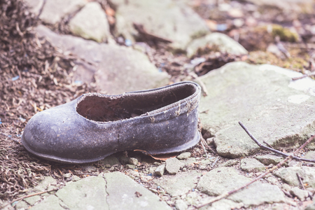 Abandoned little child shoe covered with dust in front of a  collapsed  house in Belarus, Chernobyl exclusion zone