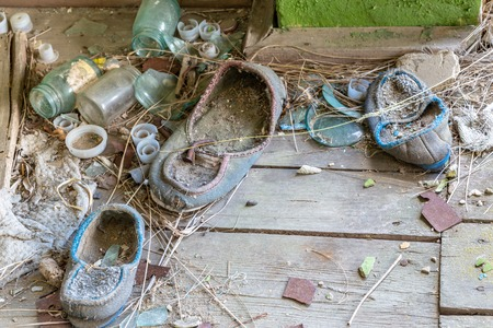 Abandoned shoes and bottles covered with dust in a  collapsed  house in Belarus, Chernobyl exclusion zone