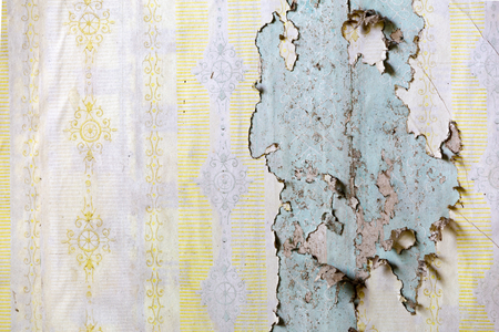 Texture of yellow wallpaper peeling form a wall on a wall in an abandoned house