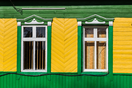 Facade and windows of a colorful little Belarus wooden house