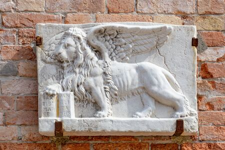 Winged lion sculpture, the symbol of Venice in Italy, on a orange wall and beside a historical window