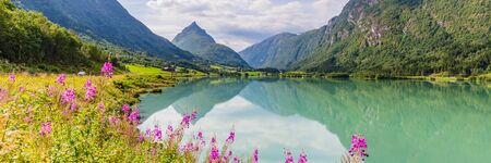 Mountain panorama with mountain Eggenipa reflecting in a lake in Gloppen along highway E39 in Sogn og Fjorden county in Norway Banque d'images - 129571939