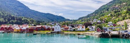 View at Solvorn, a picturesque little village with white wooden houses along Lustrafjorden on a summer day in Sogn og Fjordane county in Norway.
