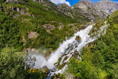 Rainbow and waterfall with melting water of the Briksdal glacier in Norway, arm of Jostedalsbreen glacier in Oldedalen valley in Norway, Scandinavia.