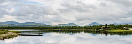 Panorama of Ringebu Kommune with view on a lake and the moutains of Rondane national Park in Oppland Norway