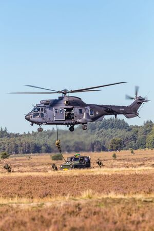 Ede, Netherlands, September 21, 2019: Cougar helicopter command S-454 of the Dutch army dropping soldiers during an air show in the Netherlands. Editorial