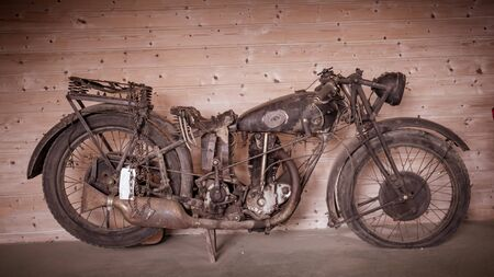 Vintage damaged motorbike parked in front of a wooden wall