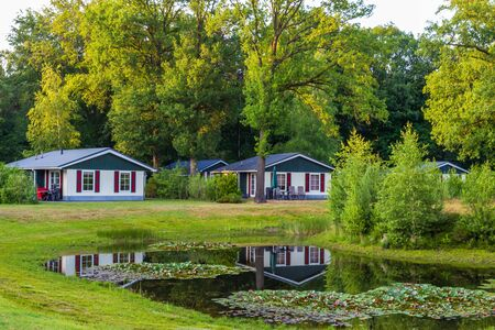 Row of colorful wooden vacation home reflected in a pond at recreation park in the middle of nature in the Netherlands