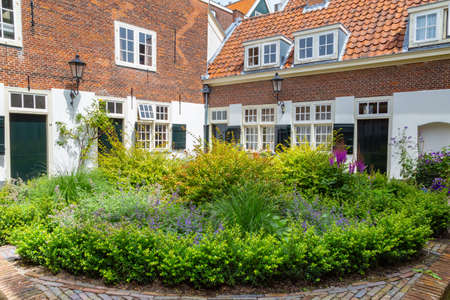 Courtyard with colroful garden and small houses in the center of city Leiden in the Netherlands, Europe