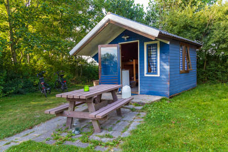 Cozy little blue wooden summer house between flowers and trees