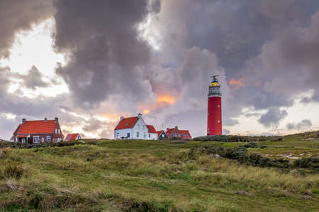Landscape with scenic view of Lighthouse during sunset with rainy clouds at Waddenisland Texel, North Holland, Netherlands Stock Photo
