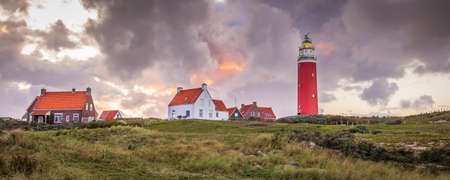 Landscape with scenic view of Lighthouse during sunset with rainy clouds at Waddenisland Texel, North Holland, Netherlands