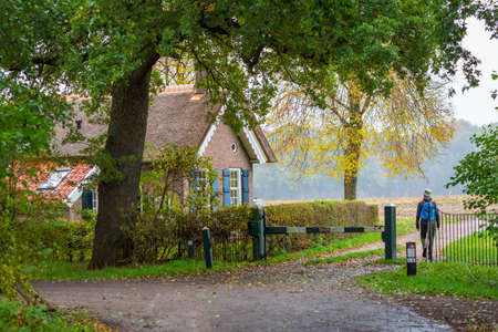 Man passing little historic toll house at entrance of Estate Dickninge in De Wolden, Drenthe , The Netherlkands