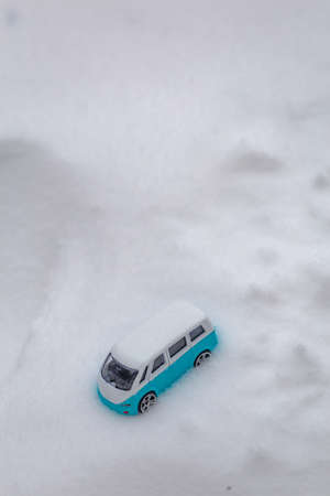 Light blue camper bus stuck in the snow Фото со стока