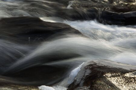 Motion of water flowing between rocks Фото со стока