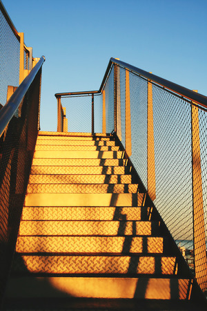 Golden metal stairs towards the roof under blue sky