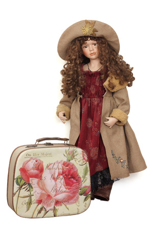 Doll in a beautiful dress with a suitcase on a white background photo