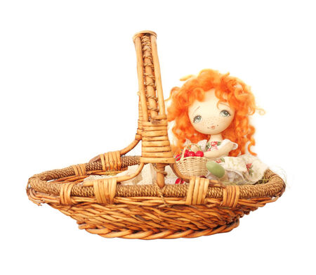 Doll with red hair and a basket on a white background photo