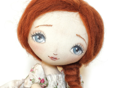 Doll with red hair on a white background photo