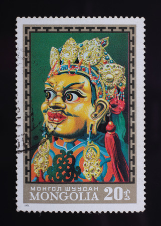 The Mongolian stamp with the image of a mask on a black background. photo