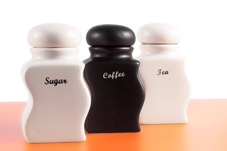 capacities: Capacities for sugar, coffee, tea on an orange surface and a white background. Stock Photo