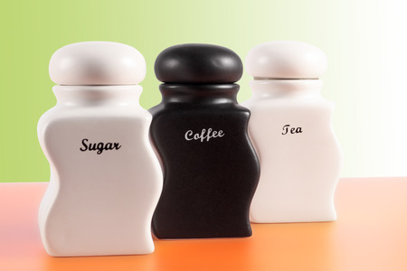 capacities: Capacities for sugar, coffee, tea on an orange surface and a green background. Stock Photo