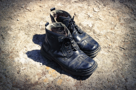 messy clothes: The thrown old winter boots on an earth background Stock Photo