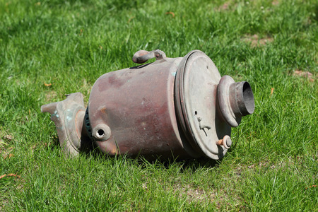 samovar: Turned, to anybody the unnecessary and forgotten old samovar lying on a grass. Stock Photo