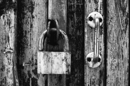 reliably: The rusty old lock and the door handle on a wood background