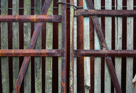 steel cable: Old rusty gate from wooden plank tied up by a steel cable Stock Photo