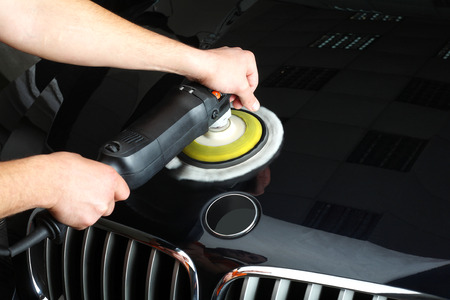 cowl: The worker polishes a car cowl with the electric tool. Close up.