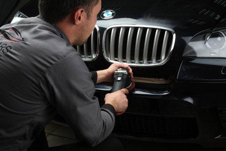 """Illustratief redactie. De werknemer poetst een bumper auto kap met de elektrische gereedschap. Auto service """"Aquacars"""". Moskou. 2015/10/04. Auto onderhoud. Detailopname Redactioneel"""
