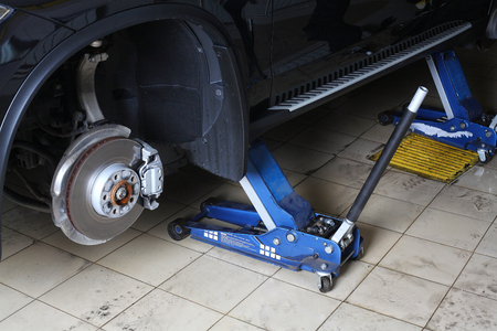 dismantled: Car repairs service. The car with the dismantled wheels on two hydraulic jacks.