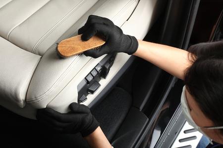autolavaggio: Lavoratore lavaggio degli interni con una spazzola morbida con schiuma.