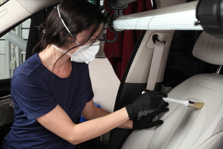 Illustrative editorial. The worker cleaning and washing of interior of the car a soft brush. Car service