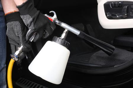 Auto onderhoud. Werknemer wassen van interieur door een speciale reinigers onder druk.