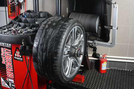 machinery machine: Illustrative editorial. Balancing tire wheel machine Hunter.  Tyre assembling. Tire balance. Car service Aquacars Moscow. Russia. 04.10.2015.