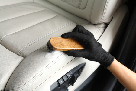 dirty car: Worker washing of interior by a soft brush with foam.