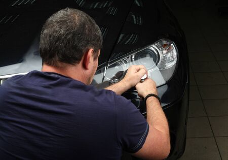 burnish: The worker polishes optics of headlights of the car with the electric tool. Close up