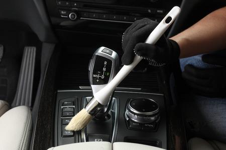 Auto service: Arbeider Het schoonmaken van onder door een zachte borstel. Stockfoto