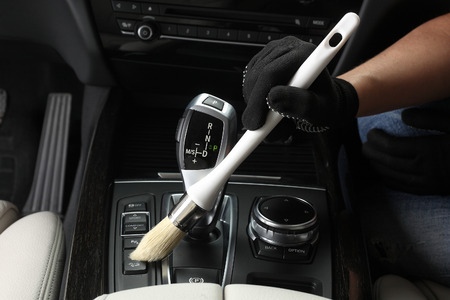 dirty car: Car service: Worker Cleaning of interior by a soft brush. Stock Photo